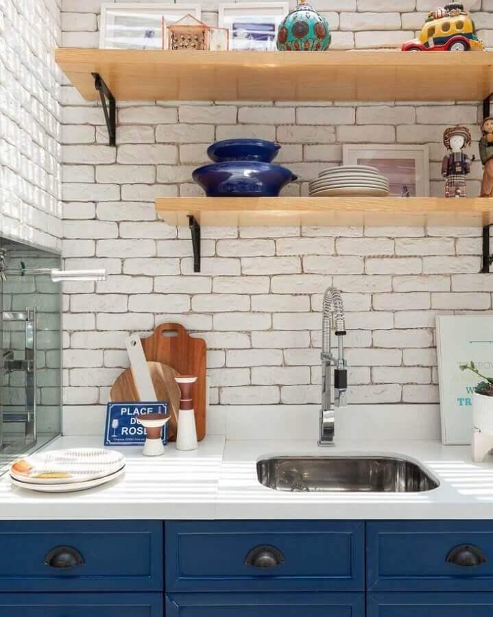 decoração com prateleira para cozinha com armários azuis e parede de tijolinho branco Foto Duda Senna Arquitetura