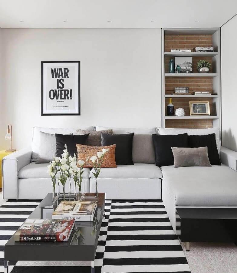 sala moderna decorada com sofá de canto e tapete listrado preto e branco Foto Novara Home