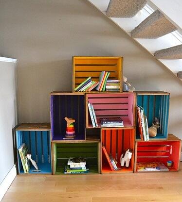 Caixotes de madeira organizando livros infantis e brinquedos