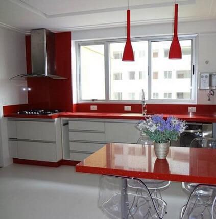 Cozinha modulada com armário branco e decoração vermelha