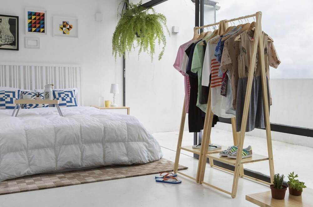 8. Decoração de quarto de casal com plantas e arara de madeira