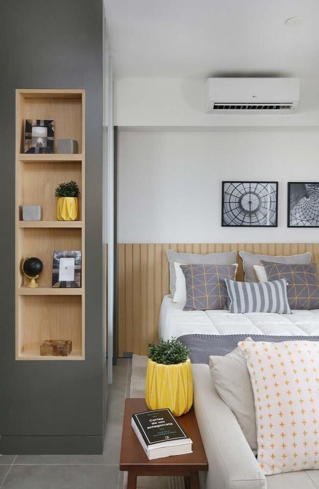 38. Decoração de quarto de casal em tons de cinza e branco, com cabeceira de madeira