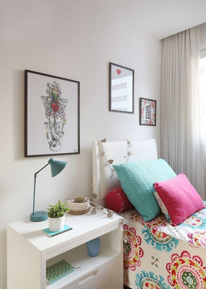 42.Decoração de quarto de solteiro com criado mudo branco, almofadas coloridas e luminária azul