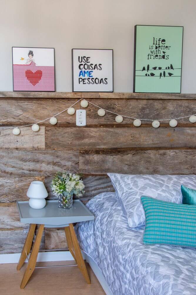 18. Decoração de quarto tumblr com cabeceira de madeira, pisca piscas e quadros