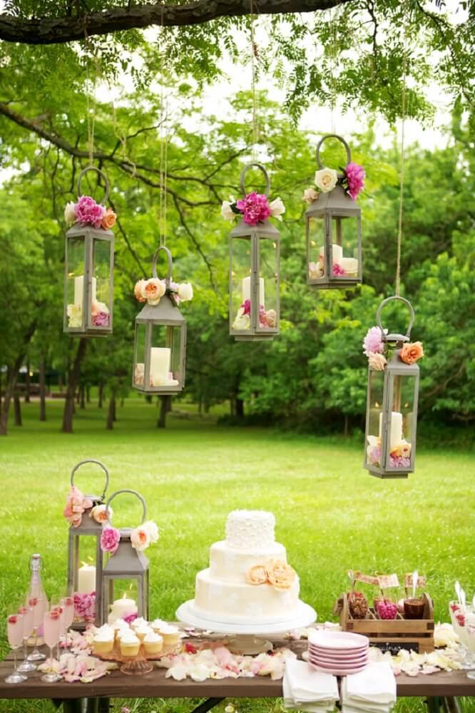 Decoração de casamento ao ar livre com velas e flores suspensas