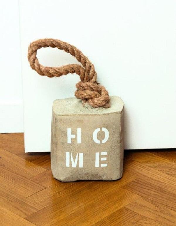 Modelo de peso de porta de concreto pintado com a palavra HOME. Fonte: Pinterest