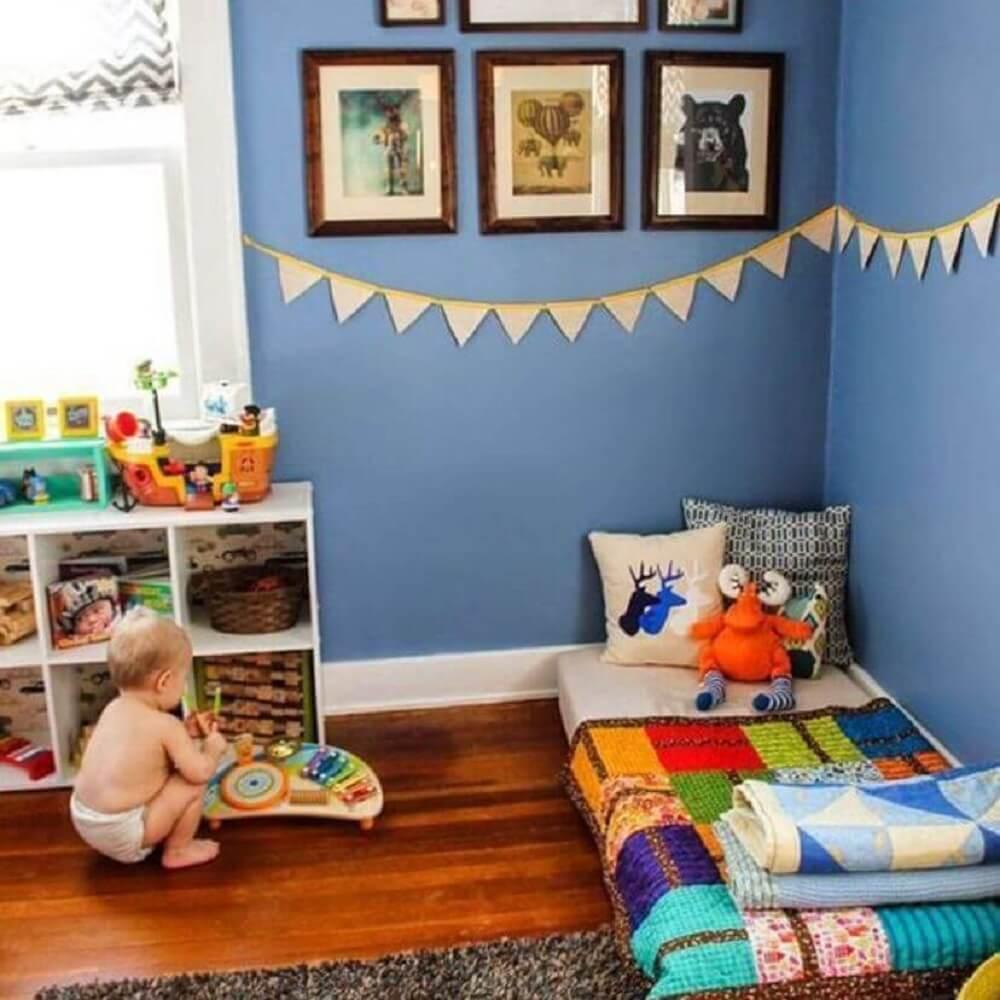 27. Modelo de quarto de menino com paredes azuis, bandeirinhas na parede e piso de madeira