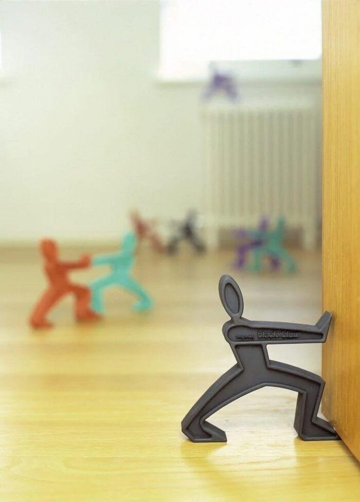 O peso de porta simula uma pessoa se esforçando para segurar a porta. Fonte: The Fun Times Guide