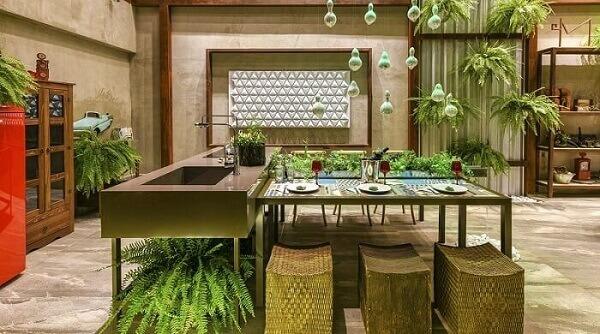 A pia de cozinha tem bancada com pés e encanta a decoração do ambiente