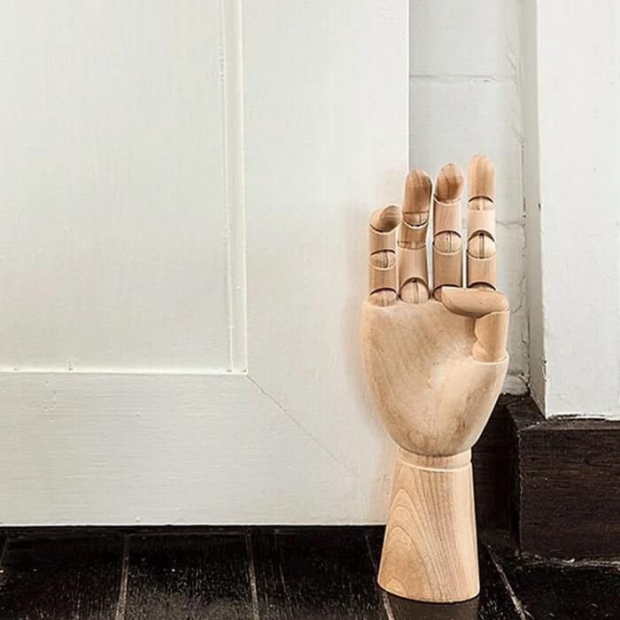 Peso de porta feito em madeira com formato de mão. Fonte: El Buen Ojo
