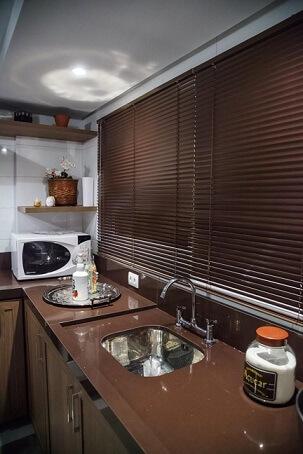 Pia de cozinha de granito marrom com cuba e torneira em inox Projeto de Braccini Lima