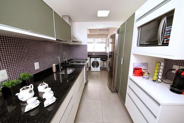 Pia de cozinha de granito preto contrastando com armários brancos e cinzas Projeto de Meyer Cortez