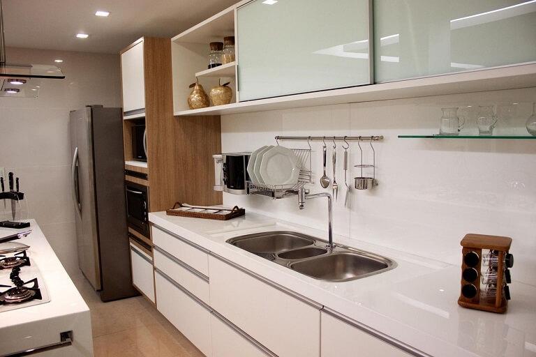 Pia de cozinha de inox em bancada de granito branco Projeto de Larissa Vinagre