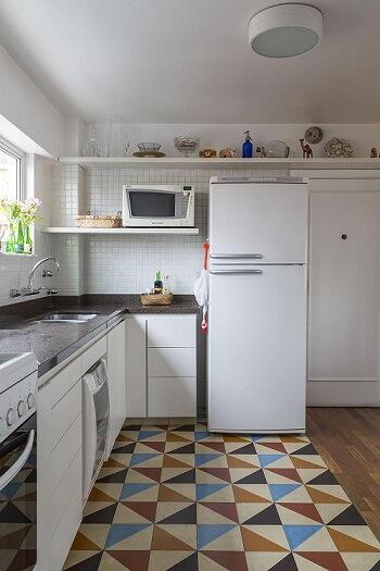 Pia de cozinha dupla de mármore escuro em cozinha com armários, prateleiras e eletrodomésticos brancos Ptojeto de Leila Dionizio