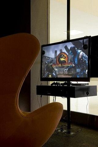 Quarto gamer com poltrona laranja Projeto de Mauricio Karam