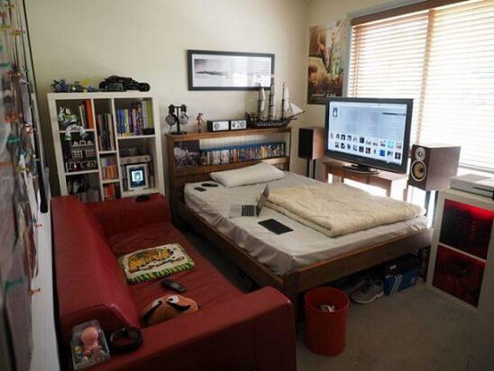 Quarto gamer pequeno com games acima da cama e TV em frente ao sofá