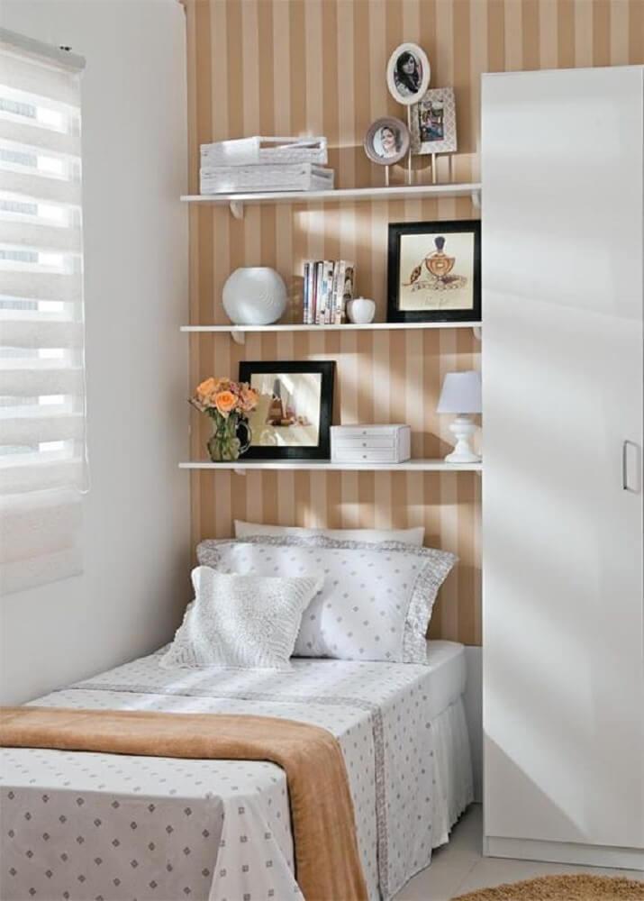 Quarto pequeno decorado com prateleiras e papel de parede