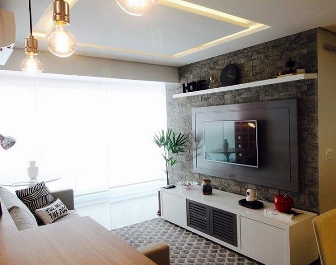 Sala de TV com papel de parede para sala imitando tijolos cinzas Projeto de Glaucio Gonçalves