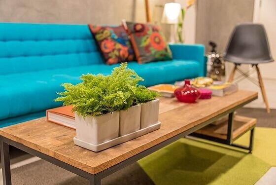 Sala-de-estar-com-mesa-de-tampo-de-madeira-e-sofá-azul-turquesa-Projeto-de-Viviane-de-Pinho