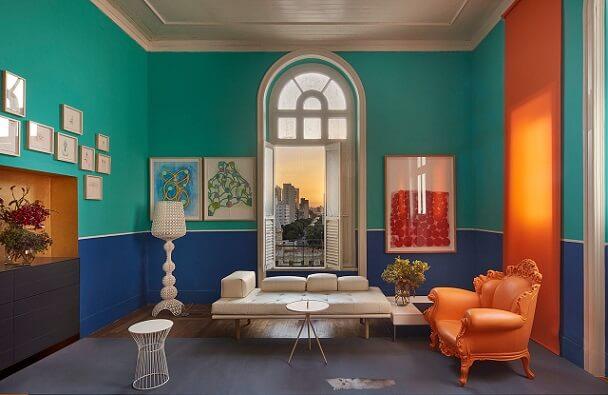 Sala de estar com paredes em azul turquesa e poltrona-laranja Projeto de Casa Cor MG 17