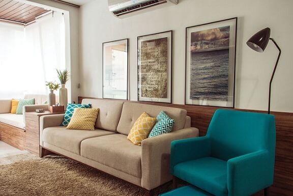 Sala de star com poltrona azul turquesa e sofás em tons de bege Projeto de Ana Carolina Campos França
