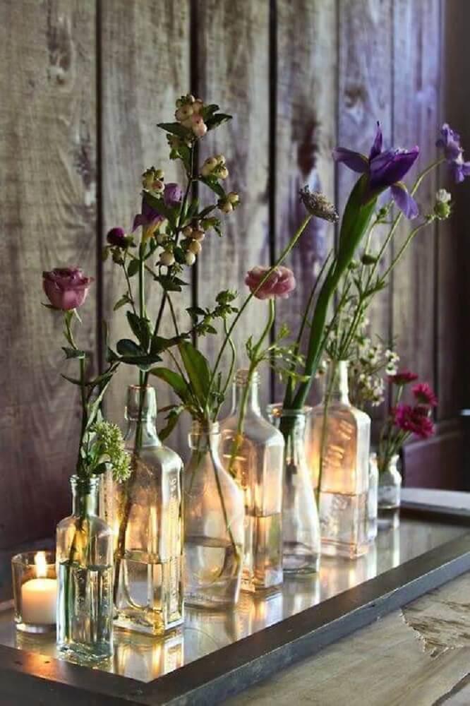 decoração feita com garrafas de vidros como vasos de flores