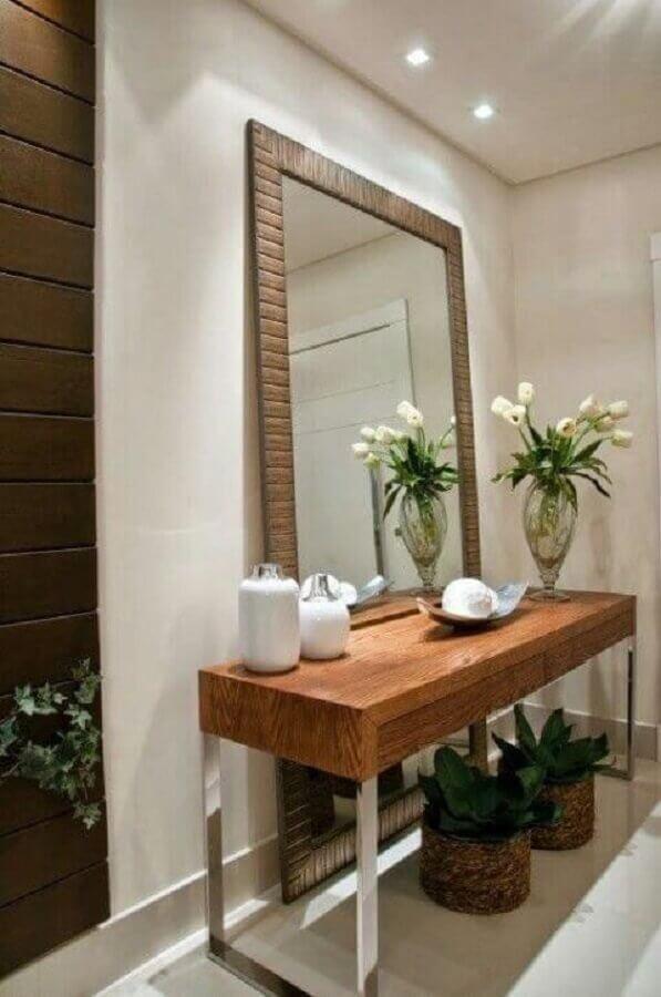 hall decorado com aparador de madeira e espelho decorativo grande Foto Duca Móveis