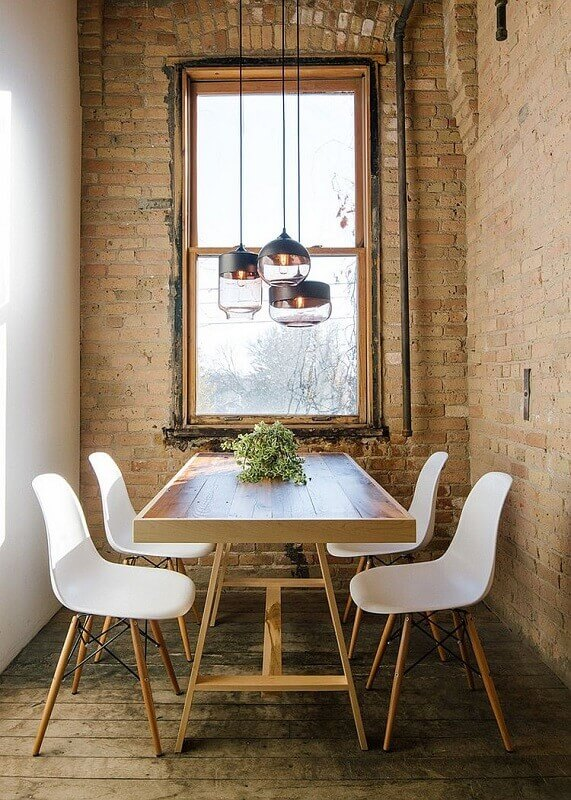 sala de jantar com parede de tijolinhos e pendentes