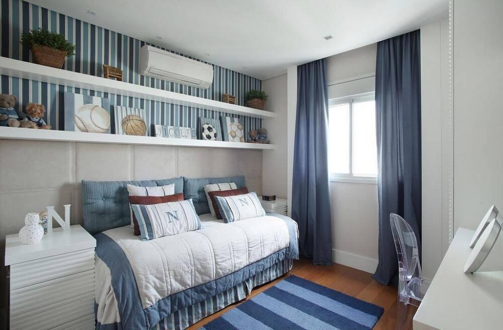 quarto de menino com papel de parede azul e prateleiras brancas