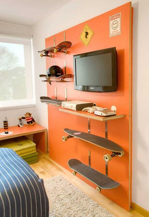 quarto gamer decorado com painel laranja para tv e com suporte para skate Foto Pinterest