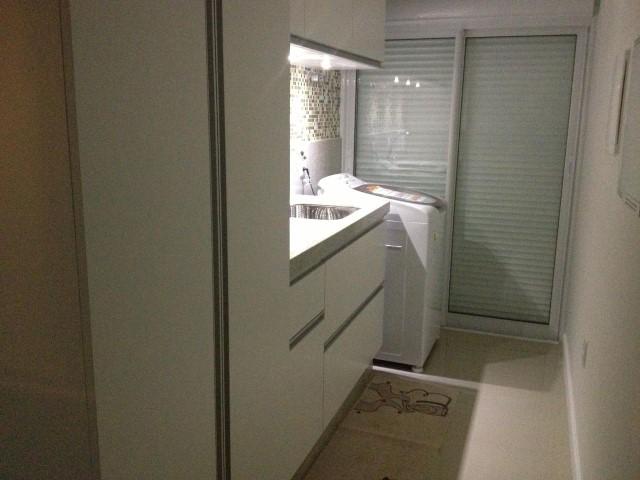 Área de serviço com armários brancos Projeto de Paula Correa Pereira