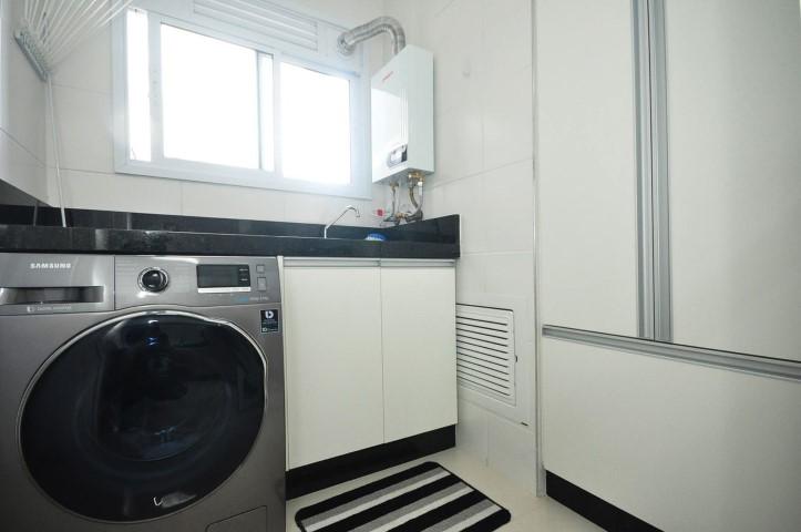Área de serviço com armários brancos e bancada preta Projeto de Condecorar