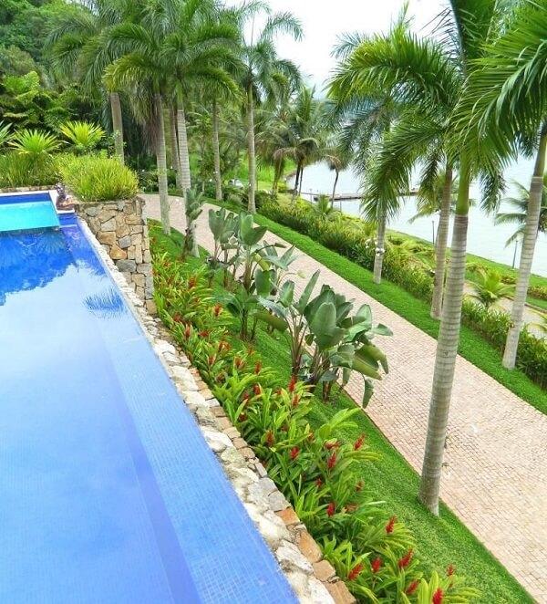 A piscina com lateral de pedra permite vista para o mar