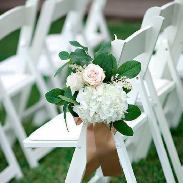 Amarre pequenas flores na cadeira dos convidados