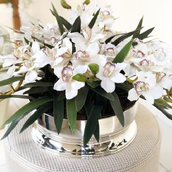 Arranjos de flores artificiais em Orquídeas decoram o centro da mesa de jantar