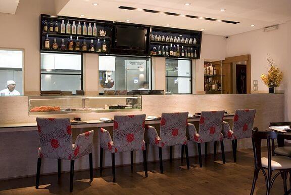 Balcão de restaurante em mármore travertino Projeto de Claudia Arakaki