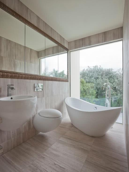 Banheiro com banheira branca e cuba combinando