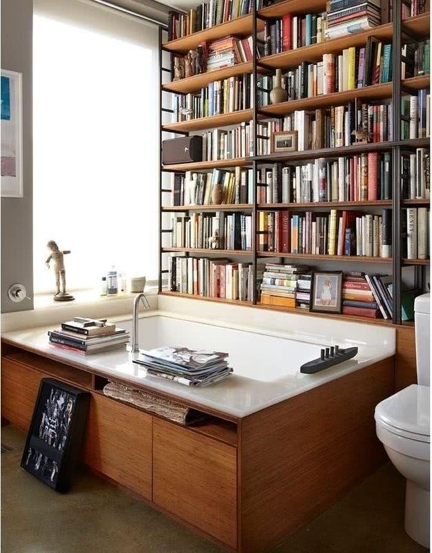 Banheiro com banheira grande e livros ao redor
