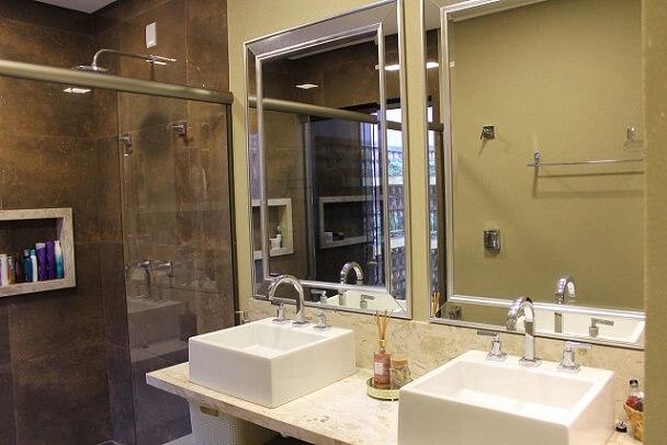 Banheiro do casal com bancada e rodabanca de mármore travertino Projeto de Bianca Monteiro