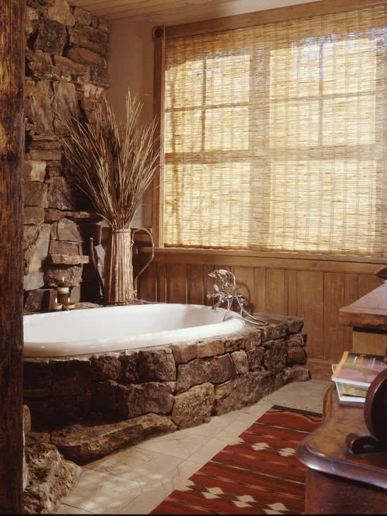Banheiro rustico com banheira revestida de pedras