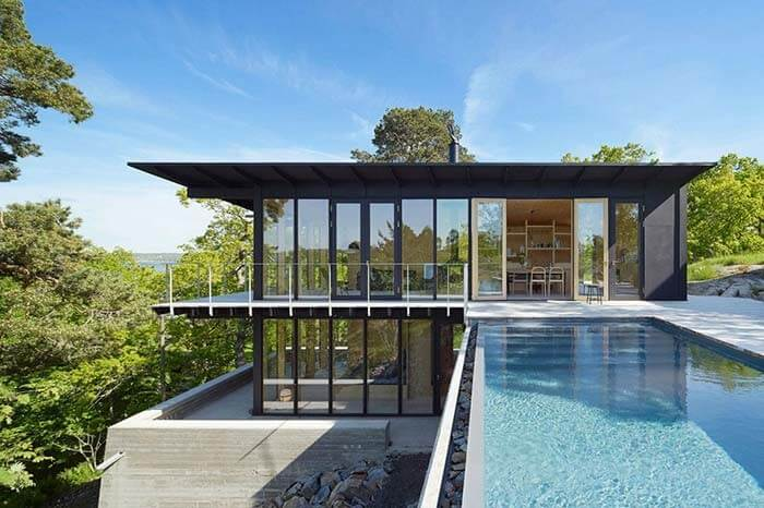 Casa de fazenda com fachada de vidros e piscina com borda infinita