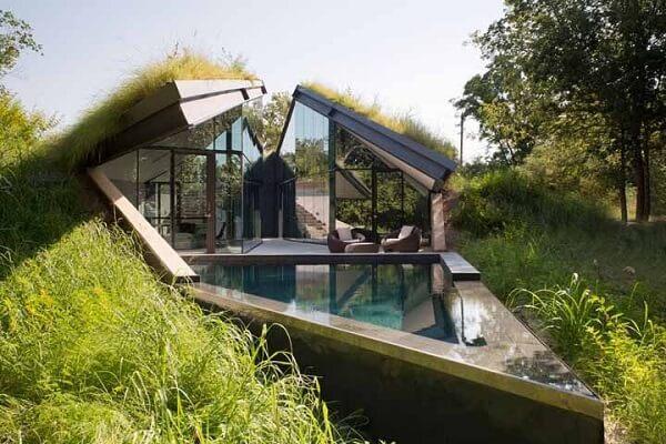 Casa de vidro com telhado verde