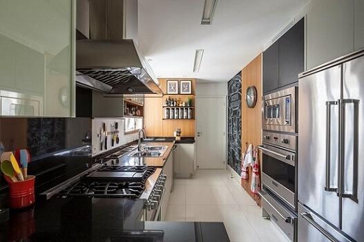 Cozinha planejada com parede de tinta lousa e armários escuros Projeto de Luciana Tomas