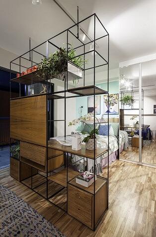 Decoração de apartamento pequeno com estante modular dividindo ambientes