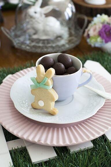 Decoração de páscoa com mini ovos em xícara e biscoito de coelho