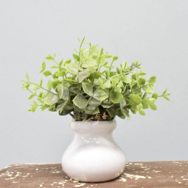 Folhagem verde criar um contraste lindo com o vaso branco