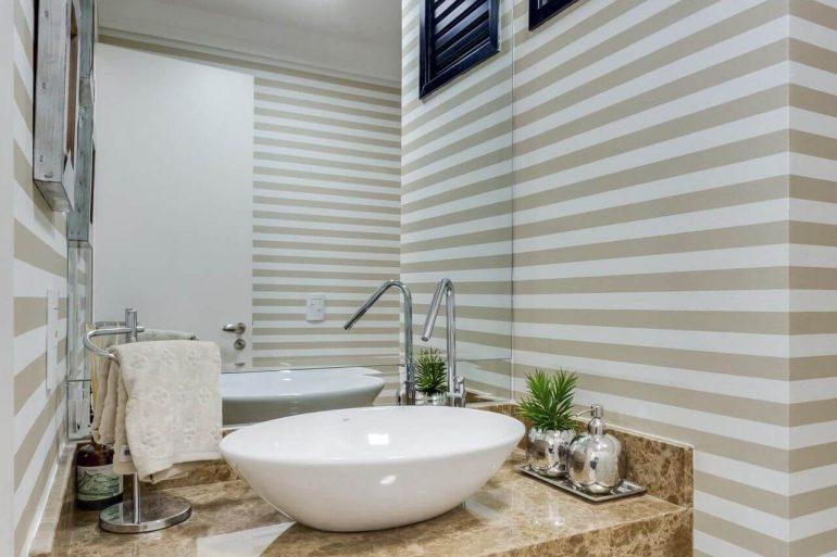 O papel de parede listrado entrou em harmonia com a bancada de mármore para lavabo decorado.