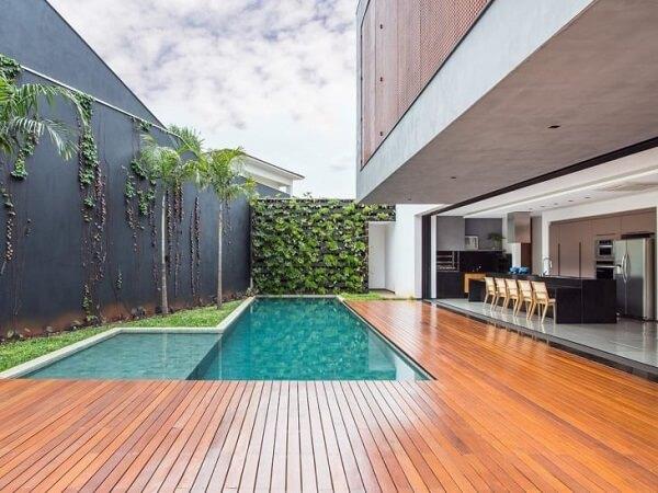 O projeto ganhou um amplo deck de madeira ao redor da piscina