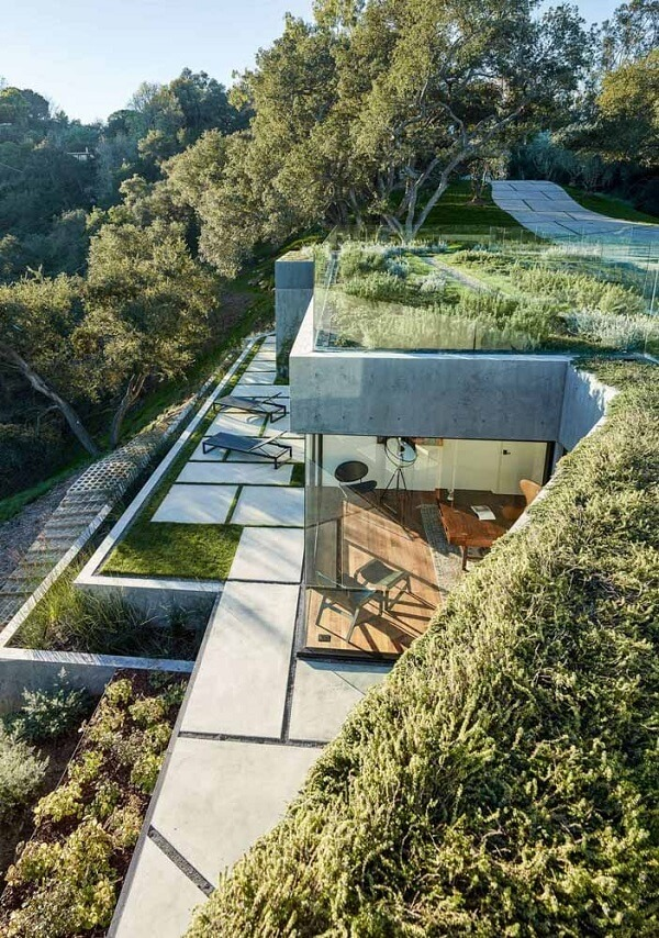 O telhado verde se mescla com a paisagem local
