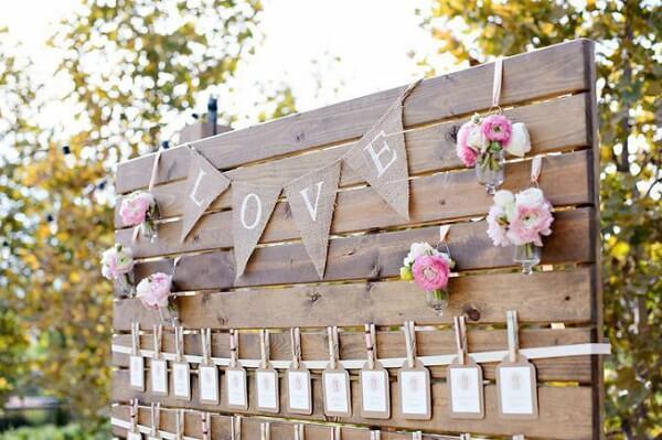 Painel de madeira com faixa de tecido juta escrito LOVE
